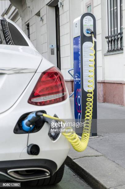Close up of white electric car being on the charge in Budapest during summer day