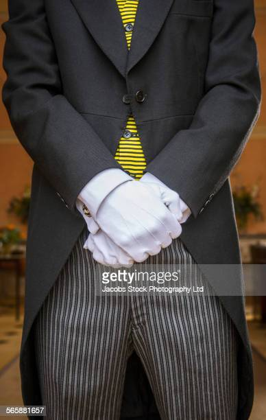 Close up of white gloves of Caucasian butler