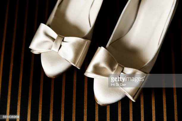 close up of white high heels with bows - white satin stock photos and pictures