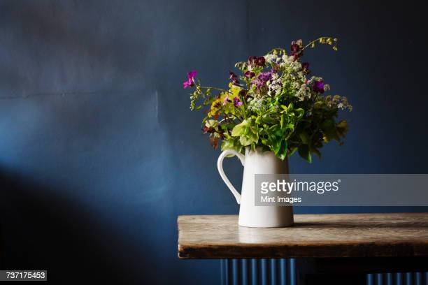 Close up of white jug with bunch of wild flowers on a wooden table, blue wall behind.