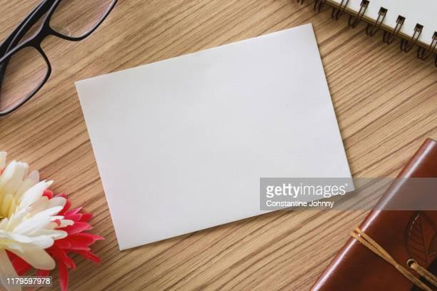 close up of white paper card on wood desk - wedding invitation imagens e fotografias de stock