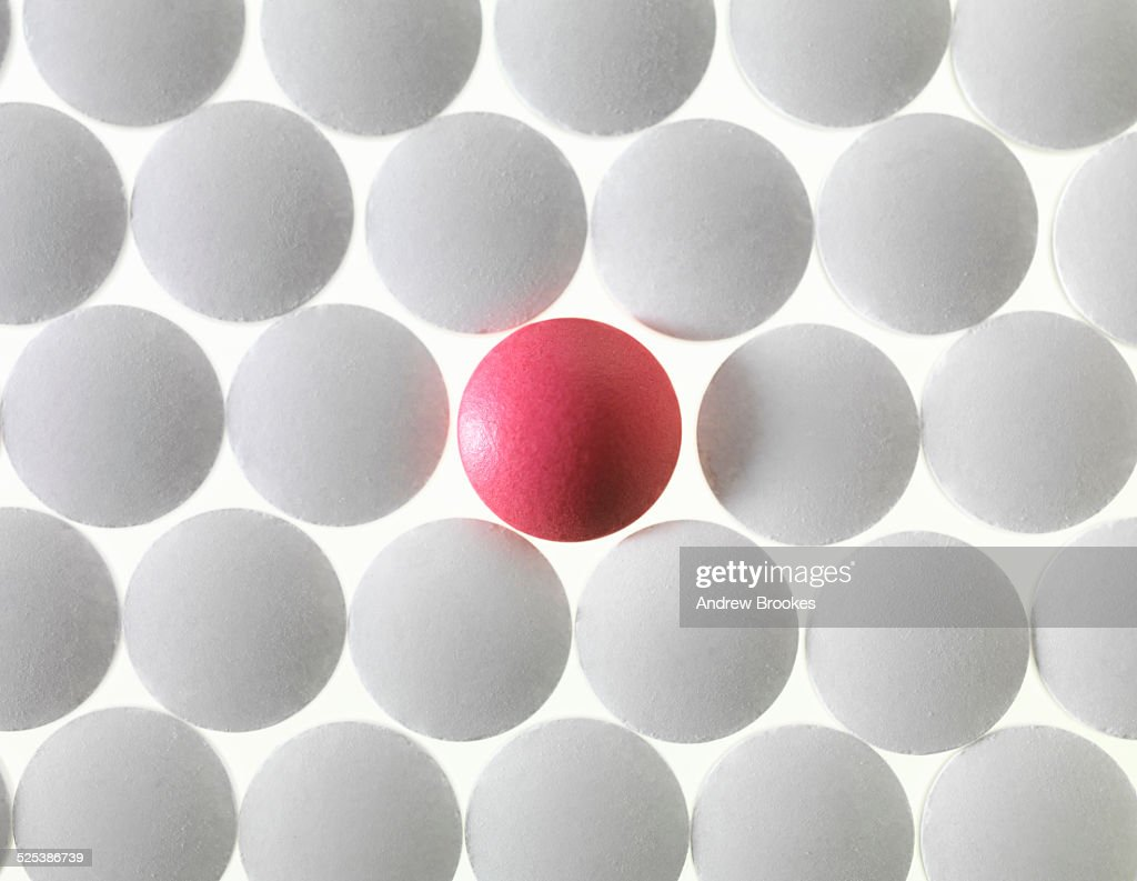 Close up of white pills and one red pill : Stock Photo