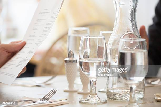 Close up of wine and water glasses and place settings at a table in a restaurant. A persons hand holding the menu.