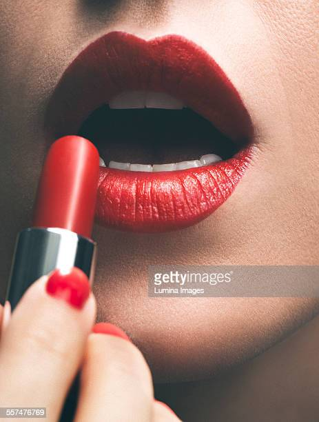 close up of woman applying red lipstick - lippenstift stock-fotos und bilder