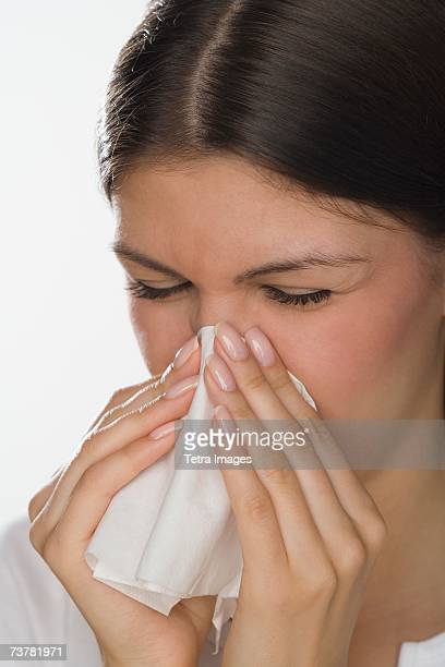 Close up of woman blowing nose
