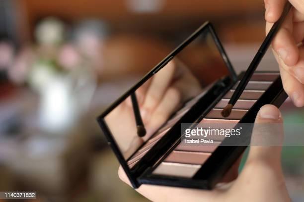 close up of woman brushing with eye shadow pallet - sombra maquiagem de olho - fotografias e filmes do acervo