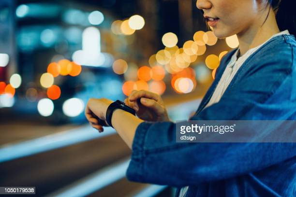 close up of woman checking smart watch in city at night, with multi coloured city street light as background - クラウドソーシング ストックフォトと画像