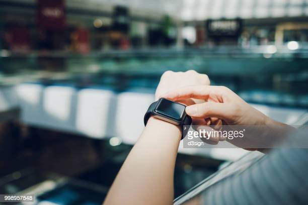 close up of woman checking the shopping list on smart watch in a shopping mall - intelligenz stock-fotos und bilder