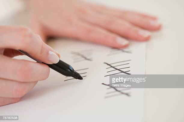 Close up of woman counting on paper