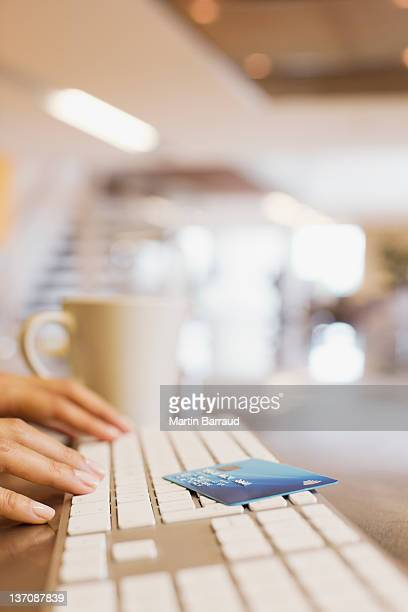 Close up of woman credit card and woman typing on keyboard