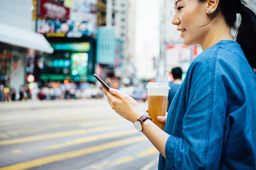 Close up of woman drinking iced drink and using smartphone while waiting in pedestrian walkway in busy urban city street - gettyimageskorea