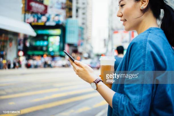 close up of woman drinking iced drink and using smartphone while waiting in pedestrian walkway in busy urban city street - fashion hong kong stock photos and pictures