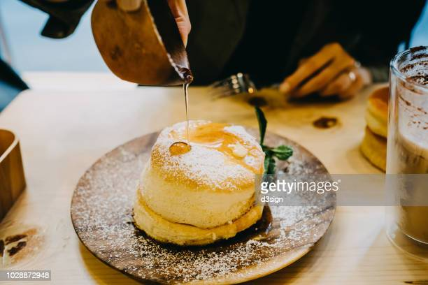 close up of woman drown the souffle pancake in maple syrup - soufflé stock-fotos und bilder
