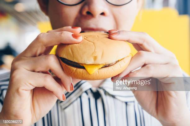 close up of woman eat a cheese burger. - hygiene stock pictures, royalty-free photos & images