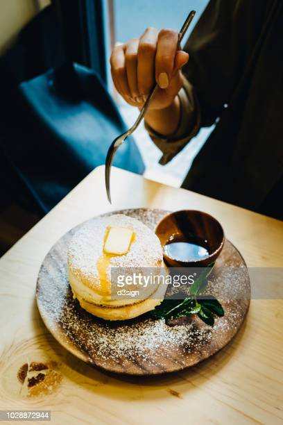 close up of woman eating fluffy pancake with butter and syrup on dinning table - soufflé stock-fotos und bilder