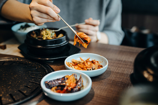 Close up of woman eating Korean appetitizer Kimchi with Bibimbap in a restaurant - gettyimageskorea