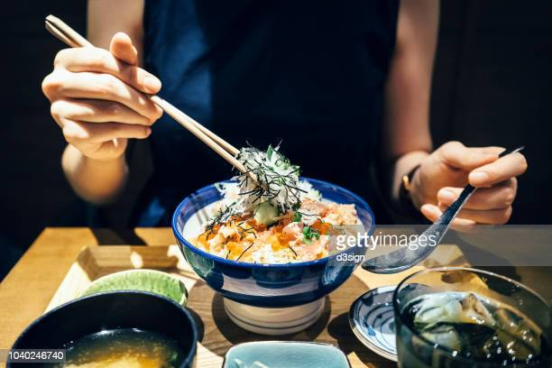 Close up of woman enjoying freshly served traditional Japanese seafood donburi with chopsticks in a restaurant