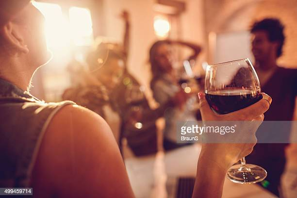 Close up of woman enjoying in wine at office party.