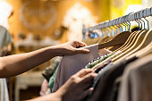 Close up of woman hand choosing thrift young and discount t-shirt clothes in store, searching or buying cheap cotton shirt on rack hanger at flea market , stall shopping apparel fashion concept