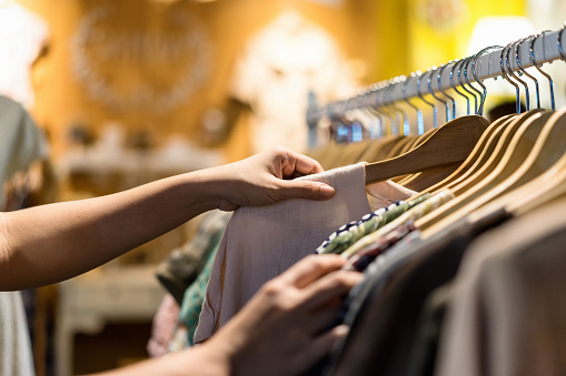 Close up of woman hand choosing thrift young and discount t-shirt clothes in store, searching or buying cheap cotton shirt on rack hanger at flea market , stall shopping apparel fashion concept 941051278