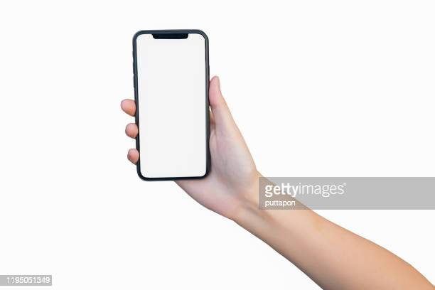 close up of woman hand holding smartphone on white background, cropped hand using smartphone on the background white - vasthouden stockfoto's en -beelden