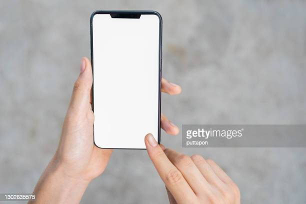 close up of woman hand holding smartphone on white background, cropped hand using smartphone on the background of polished cement - image stock pictures, royalty-free photos & images
