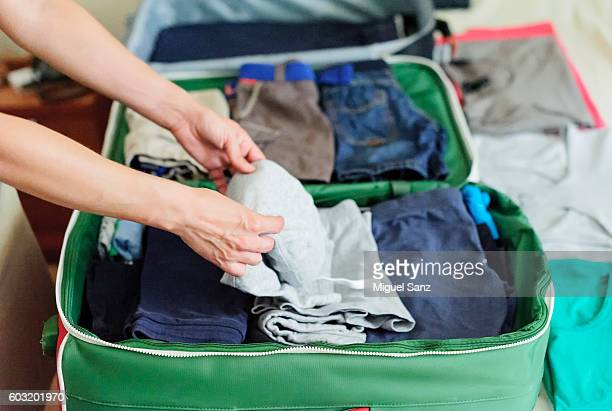 close up of woman hands packing suitcase on the bed - packing stock pictures, royalty-free photos & images