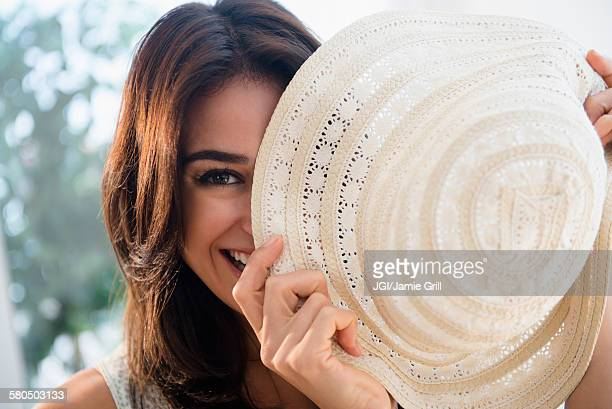 close up of woman hiding behind sun hat - sun hat stock pictures, royalty-free photos & images