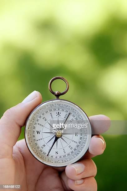 Nahaufnahme von Frau hält einen Kompass vor grünem Hintergrund.