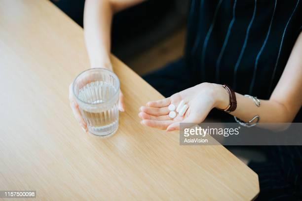 close-up van de vrouw met een glas water en medicijnen in haar hand - medicijnen innemen stockfoto's en -beelden