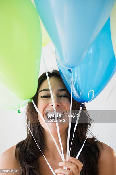 Close up of woman holding bunch of balloons