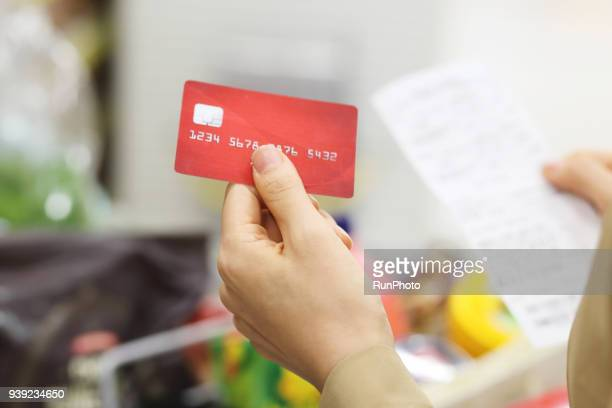 close up of woman holding credit card with shopping list  in supermarket - caisse photos et images de collection
