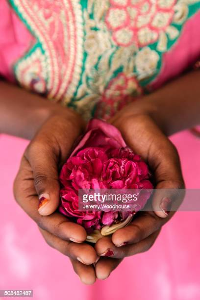 Close up of woman holding flower in cupped hands