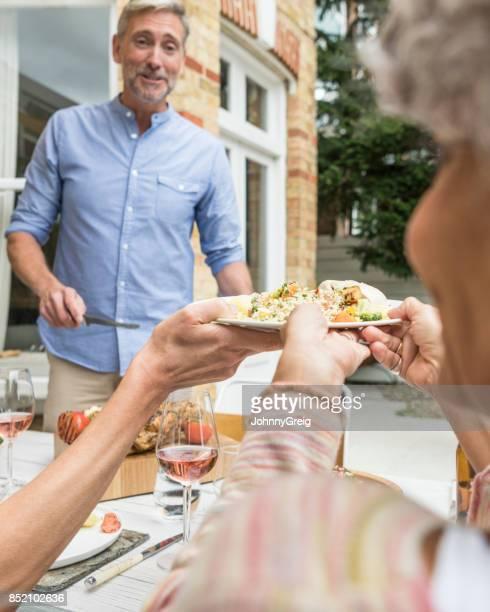 gros plan de femme tenant des aliments avec homme souriant - couscous photos et images de collection