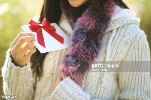 close up of woman holding gift card - cartão de presente - fotografias e filmes do acervo