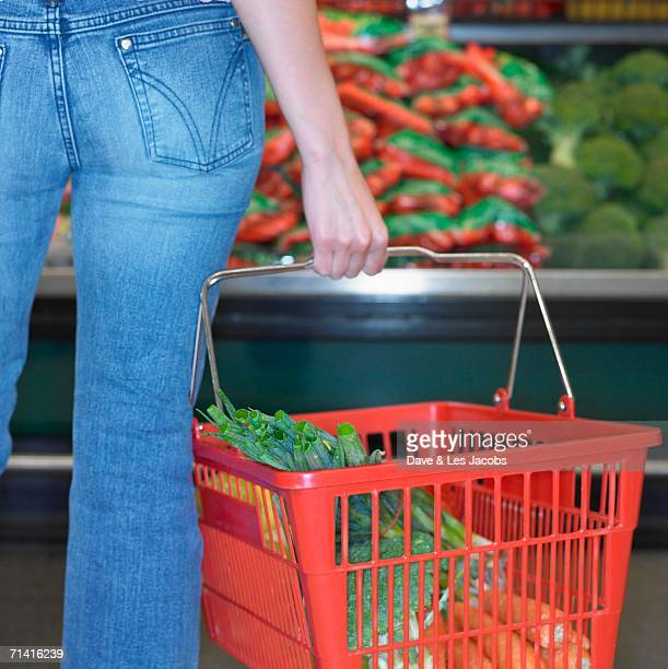 Close up of woman holding grocery basket at supermarket