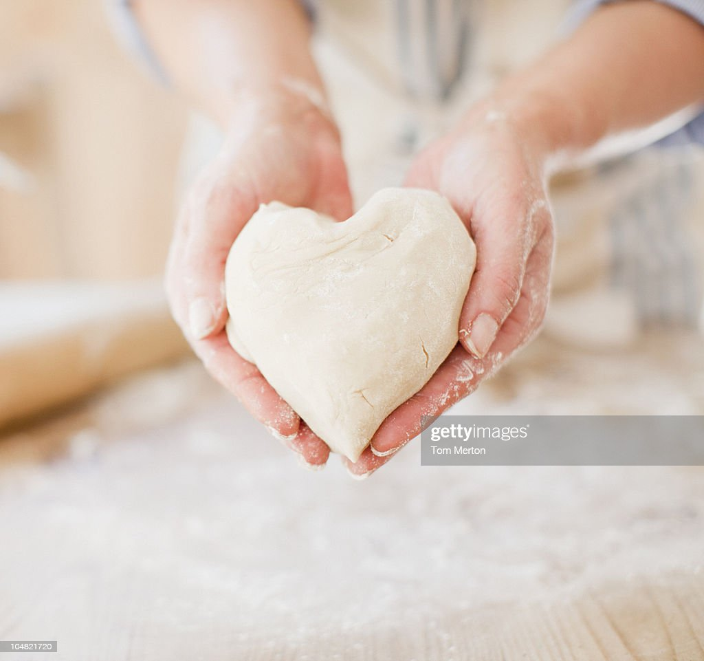Close up of woman holding heart-shape dough : Stock Photo