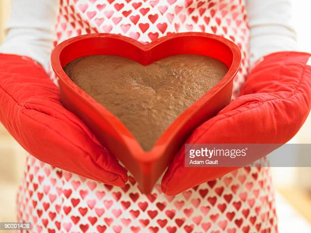 Close up of woman holding heart-shaped cake