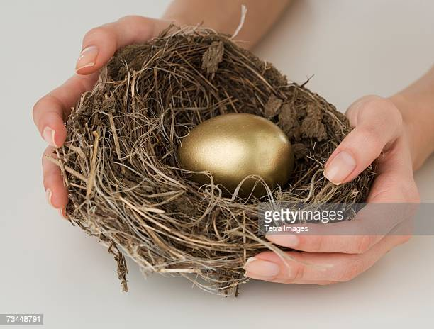 Close up of woman holding nest with golden egg