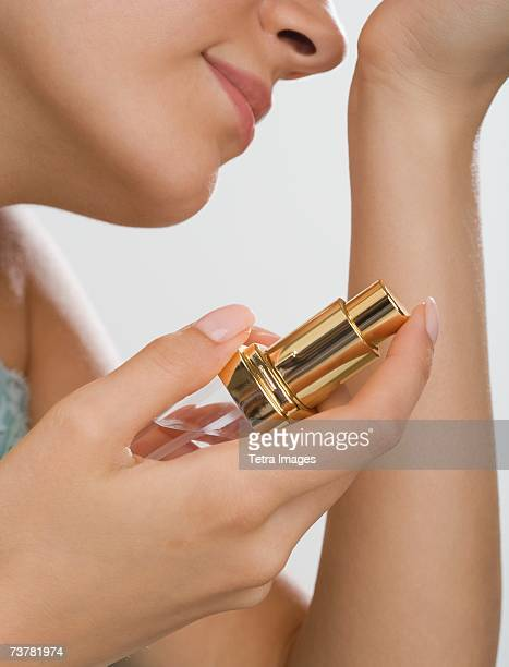 Close up of woman holding perfume and smelling wrist