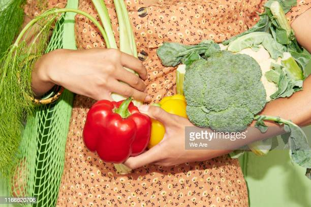 close up of woman holding vegetables - vegetarianism stock pictures, royalty-free photos & images