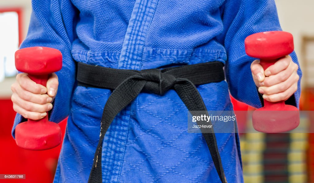 Close Up Of Woman In Blue Judo Gi And Black Belt Which Is Train With