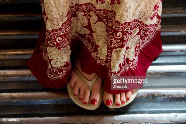 close up of woman in traditional skirt and flip flops - pretty asian feet stock photos and pictures