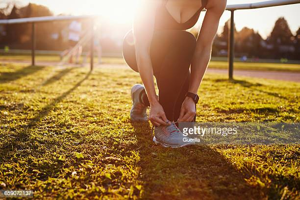 Close Up Of Woman Lacing Trainers Before Outdoor Exercise