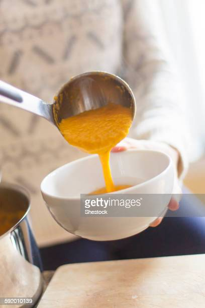 close up of woman ladling bowl of soup - ladle stock photos and pictures