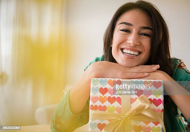 Close up of woman leaning on wrapped gift