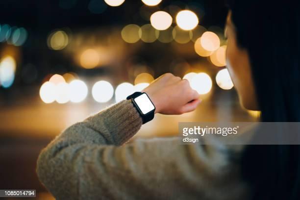 close up of woman looking at smart watch in city at night - kleine uhr stock-fotos und bilder