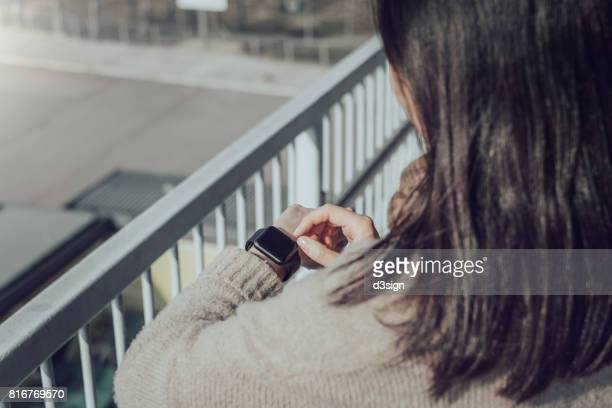 Close up of woman looking at smart watch in city