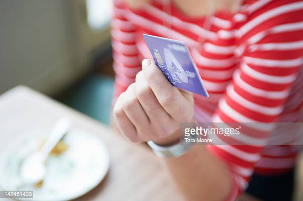 close up of woman paying with credit card at cafe