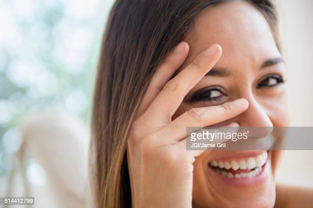 Close up of woman peering through fingers